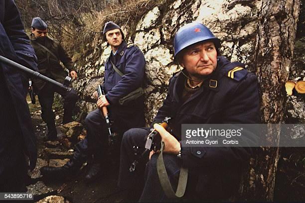 Bosnian militiamen wearing Serbian uniforms rest in Sarajevo's heights