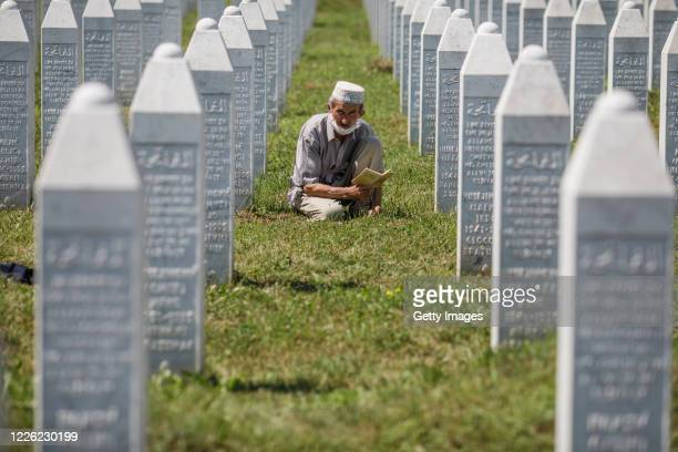 Bosnian Muslim man reads a religious book between graves on July 11, 2020 as newly identified victims are buried at the cemetery for victims of...