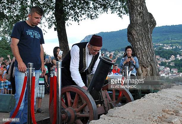 A Bosnian Muslim man wearing a traditional Bosnian outfit prepares to fire a canon from a vantage point overlooking Sarajevo to mark the end of daily...