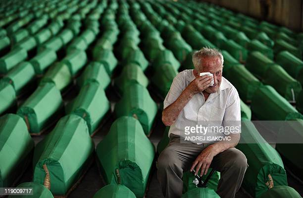 A Bosnian muslim man wipes his eye with a handkerchief as he mourns among caskets at Potocari Memorial Cemetery near Srebrenica on July 10 2011 This...