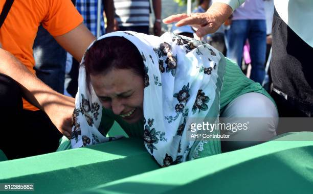 A Bosnian Muslim women expresses her grief as she mpourns over the casket of her brother one of 71 victims of the 1995 Srebrenica massacre at the...
