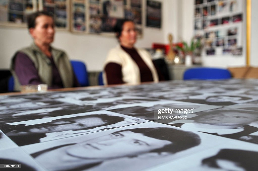 Bosnian Muslim women, Sabaheta Fejzic (L) and Kadira Gabeljic (R), survivors of the 1995 massacre in the Eastern-Bosnian town of Srebrenica, gather in Sarajevo on December 12, 2012 to watch a live television broadcast of the final ruling in the case of former Bosnian Serb general Zdravko Tolimir before the International War Crimes Tribunal for former Yugoslavia (ICTY) in The Hague. The UN's Yugoslav war crimes court found Tolimir guilty of genocide on December 12 for his role in the 1995 Srebrenica massacre, Europe's worst atrocity since World War II, and sentenced him to life in jail.
