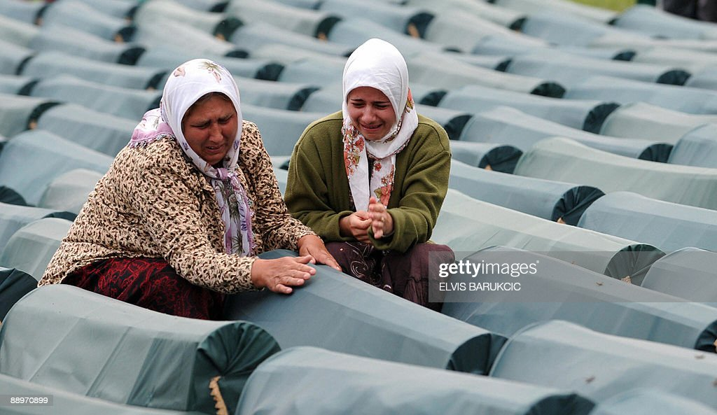 Bosnian Muslim women weep by the coffin of her relative among coffins of Srebrenica victims displayed at the memorial centre of Potocari near Srebrenica on 10 July, 2009. The 534 bodies were excavated from mass-graves in Eastern Bosnia and were identified as Muslims killed by Bosnian-Serb forces in the Srebrenica area. Bosnian Serb troops massacred up to 8,000 Bosnian Muslim men after capturing Srebrenica on 11 July, 1995, during the 1992-1995 war in Bosnia-Herzegovina. The 534 identified victims will be buried on July 11 in the Memorial Center Potocari, next to some 3,500 victims of the massacre already buried there.