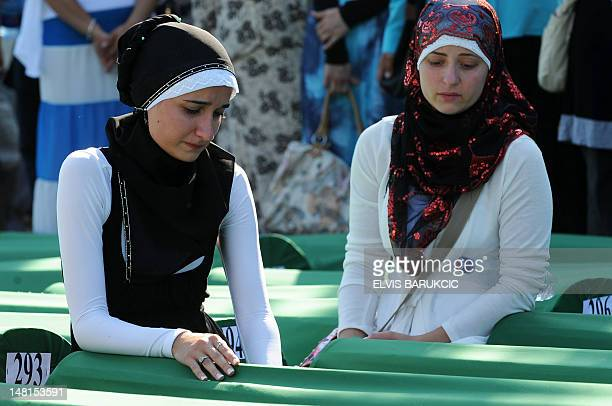 Bosnian Muslim women weep over remains of their relatives among 520 body caskets laid out in preparation for a mass burial ceremony at the...