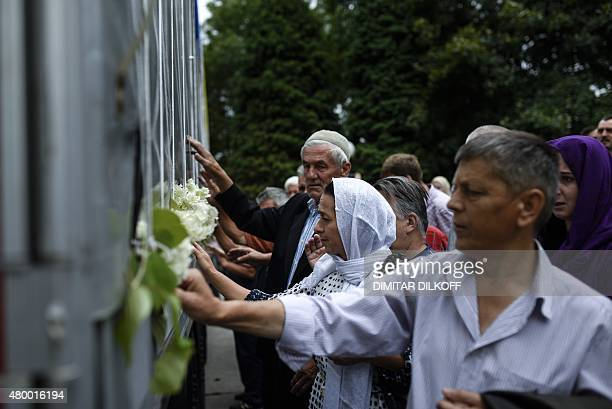 Bosnian muslims reacts as they touch a truck carrying 136 coffins of newly identified victims of the 1995 Srebrenica massacre in the town of Visoko...