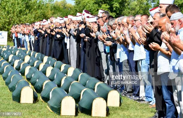 Bosnian Muslims, survivors of massacre in Western-Bosnian town of Prijedor in 1992, pray near body caskets of their relatives, as they are prepared...