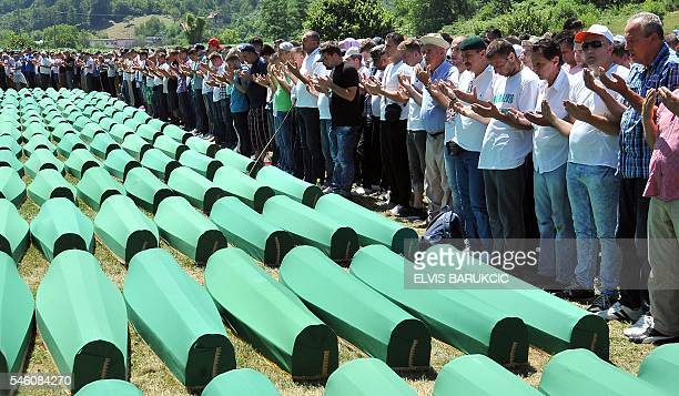 Bosnian Muslims survivors of Srebrenica 1995 massacre pray near body caskets of their relatives layed out at memorial cemetery in village of Potocari...