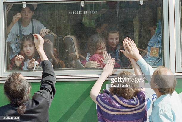 Bosnian parents say goodbye to their children as a convoy takes them out of wartorn Sarajevo to Italy