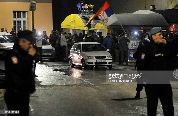 Bosnian police control streets while a group of Bosnian Serbs wave Serbia's national flag as they gather in the center of the eastern Bosnian town of...
