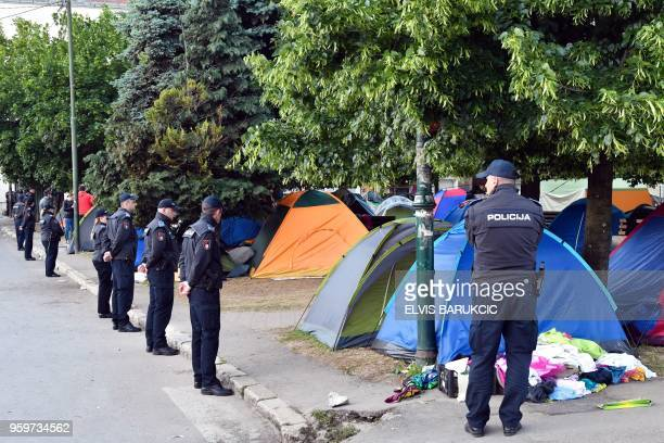 Bosnian police officers stand guard as migrants pack their belongings and their tents during the evacuation of a makeshift camp in a park across the...