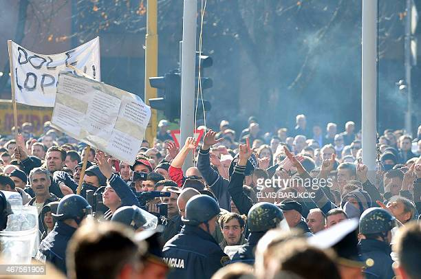 Bosnian police stand opposite protesters gathered in front of a local government building in the northern Bosnian town of Tuzla on February 7 2014...