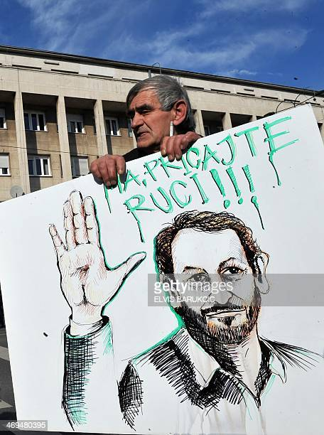 A Bosnian protester hold a placards depicting Bakir Izetbegovic leader of ruling Bosniak Muslim Party with the slogan Talk To The Hand during a...