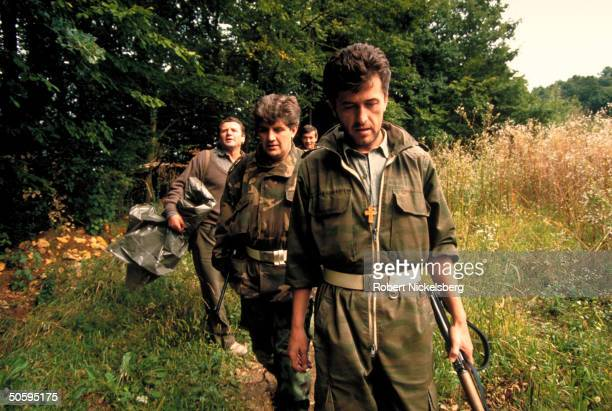 Bosnian Serb troops marching in forestframed field in Muslimsurrounded Serbian civil war front in exYugoslav republic