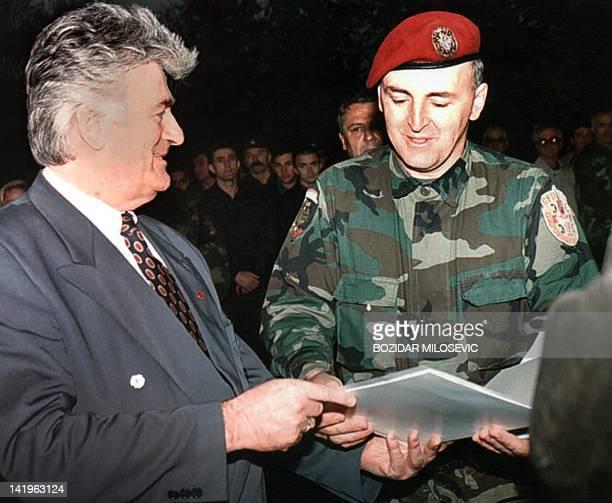Bosnian Serbe leader Radovan Karadzic hands over a certificate of graduation to Zeljko 'Arkan' Raznatovic commander of the Serbian Voluntary Forces...