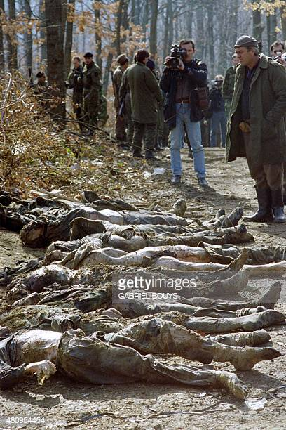 Bosnian Serbs look at the body of 24 mutilated men discovered in a mass grave in Eastern Bosnian village of Kamenica on February 17 1993