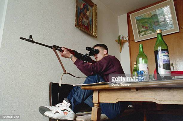 A Bosnian sniper attempts to shoot Serbian snipers in the mountains from his position on the 20th floor of a Sarajevo building