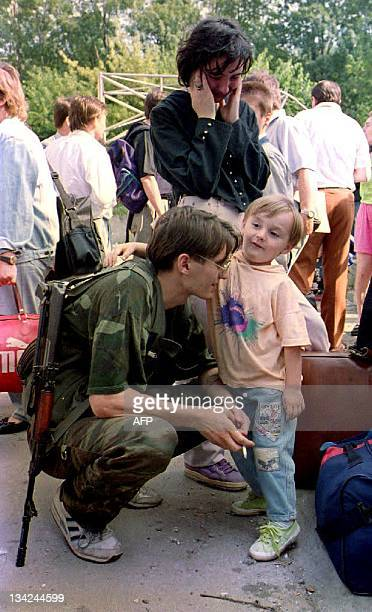 A Bosnian soldier gathers with his family before their departure from Sarajevo 12 August 1992 Serbian forces have agreed to safe passage to about 350...