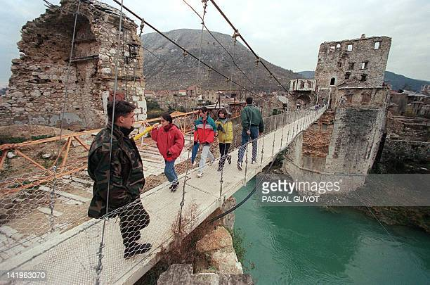 A Bosnian soldier is pictured 17 December on a hanging footbridge which replaced the old bridge of Mostar The Mostar bridge which was bombed out in...