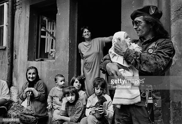 Bosnian soldier Sead Hamzic holds his 53 day old goddaughter Amila outside the family home in Sarajevo shortly before going off to the frontline to...