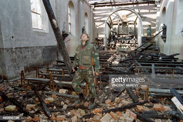 A Bosnian soldier surveys the destroyed church in Stup on March 23 1993 Stup on the road between Sarajevo and the airport has been the scene of...
