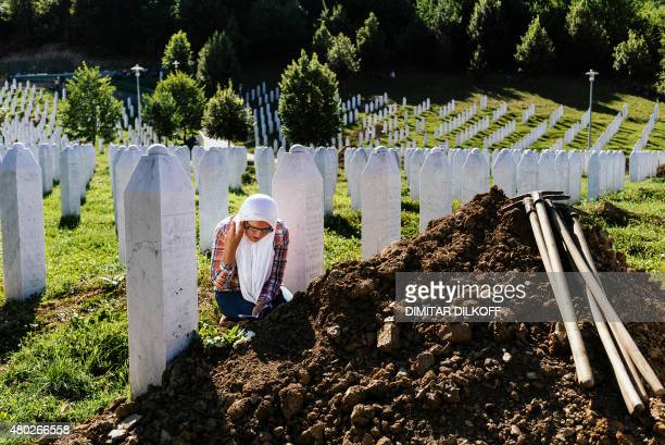A Bosnian woman mourns nex to the grave of a relative at the Potocari Memorial Center near the eastern Bosnian town of Srebrenica on July 10 where...
