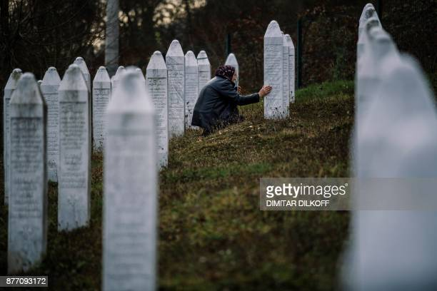 A Bosnian woman pray near a grave of her relative at the memorial center of Potocari near Srebrenica on November 21 2017 On November 22 ICTY judges...