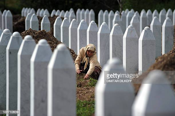 A Bosnian woman tidies up a newly dug grave in the Potocari memorial cemetery near Srebrenica on July 8 2010 This year's mass burial of the remains...