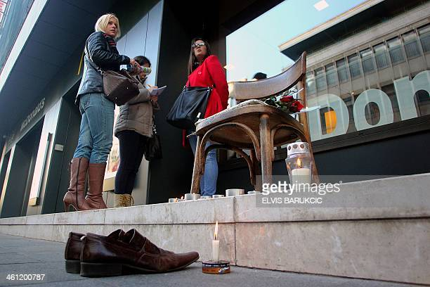 Bosnian women stand next to a makeshift memorial for legendary shoecleaner 'uncle' Miso on a main street in Sarajevo on January 7 2014 Sarajevans...