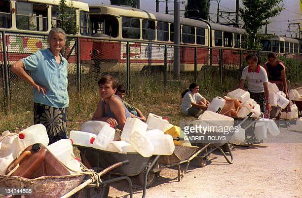 Bosnian women wait in line with their water containers 17 August 1993 sheltered by streetcars in Sniper Alley. A Bosnian Croatian spokesman, Drago...