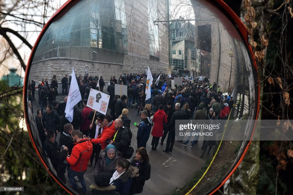 Bosnian workers of several state owned or partially state owned companies, hold placards as they demonstrate in front of the government building in Sarajevo, on January 24, 2018 to protest against ...