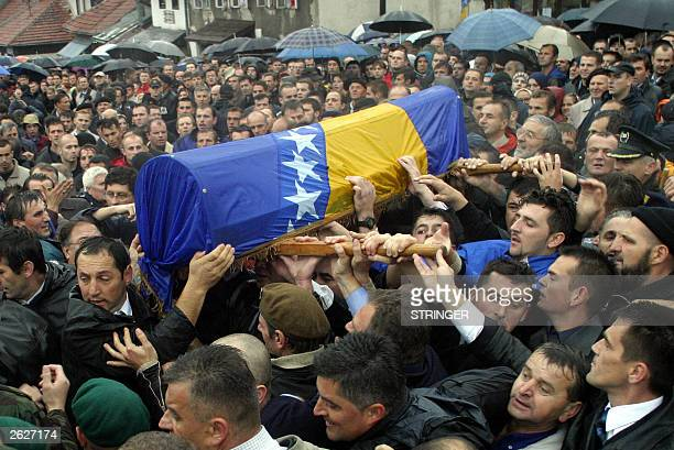 Bosnians carry the body of former president Alija Izetbegovic wrapped in the national flag during his funeral procession in Sarajevo 22 October 2003...
