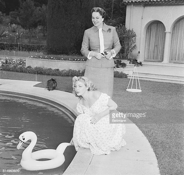 Bosomy Russian beauty Irina Skobtseva launches a swan float in the pool at the Aga Khan's luxurious villa Yakimoor Looking on is the Moslem ruler's...