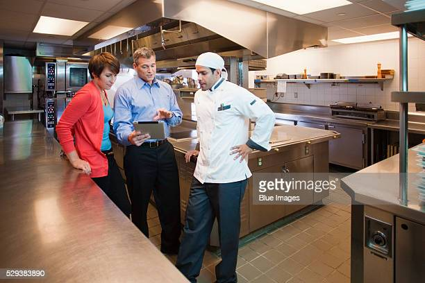 Boss and chef looking at tablet pc in restaurant kitchen