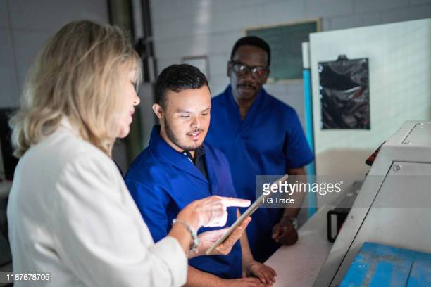 boss and employee working together in industry - persons with disabilities stock pictures, royalty-free photos & images