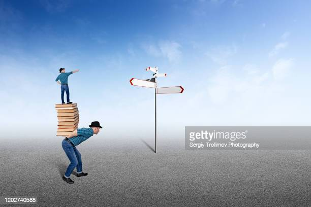 boss is standing on back of employee and showing the direction - road sign board stock pictures, royalty-free photos & images