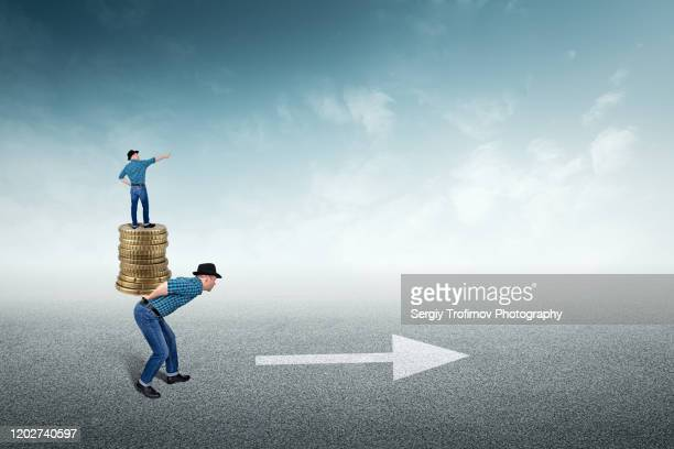 boss is staying on stack of coins and employee carrying him - road sign board stock pictures, royalty-free photos & images