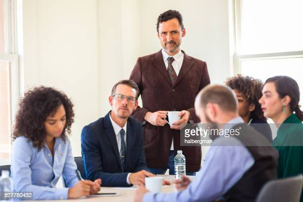 Boss Smiling at Camera Over Heads of Office Workers in Conference
