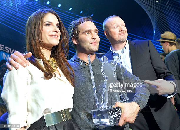 Bosse of Niedersachsen stands with entertainer Stefan Raab and moderator Sandra Riss after winning the Bundesvision Song Contest 2013 at SAP Arena on...