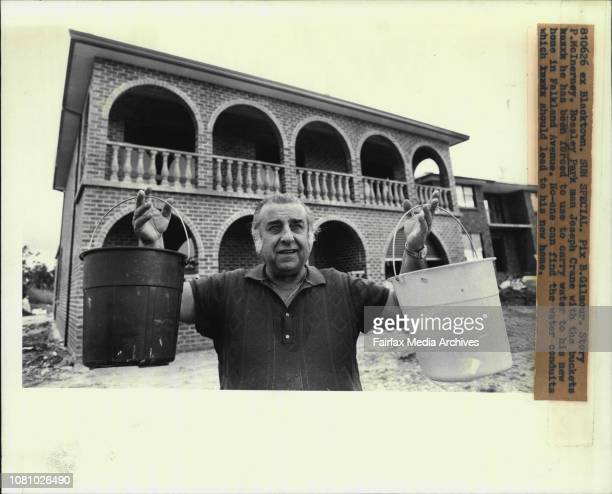 Bossley Park man Joseph Crane with the buckets he has been forced to use to carry water to his new home in Falkland Avenue Noone can find the water...