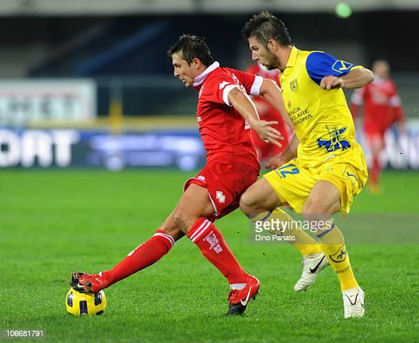 Bostjan Cesar of Chievo competes with Vitali Kutuzov of Bari during the Serie A match between AC Chievo and AS Bari at Stadio Marc'Antonio Bentegodi...