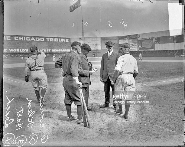 Boston Braves baseball player Evers and Chicago Cubs baseball player Leach standing with Klem and umpire Hart behind home plate on the field at West...