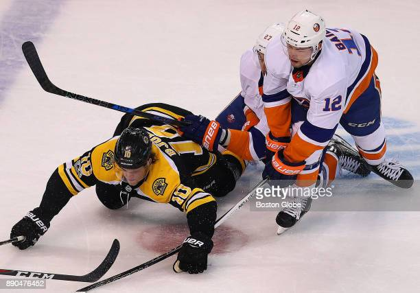 Boston Bruins' Anders Bjork collides with Islanders' Anders Lee and Josh Bailey while chasing a loose puck in the first period The Boston Bruins host...