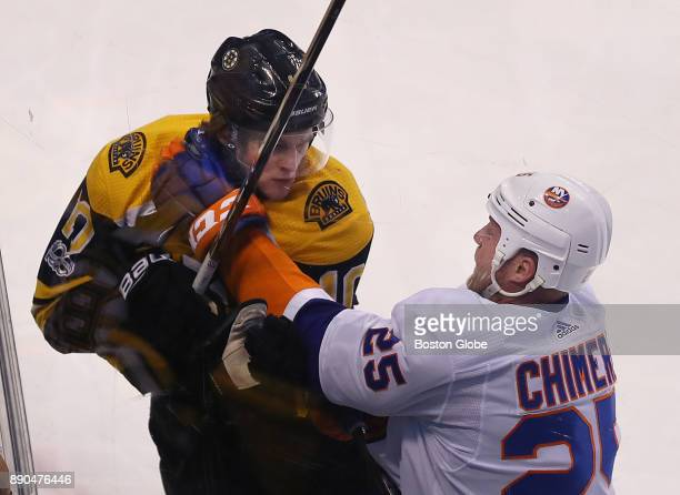 Boston Bruins' Anders Bjork gets a glove to the face by Islanders' Jason Chimera in the first period The Boston Bruins host the New York Islanders in...
