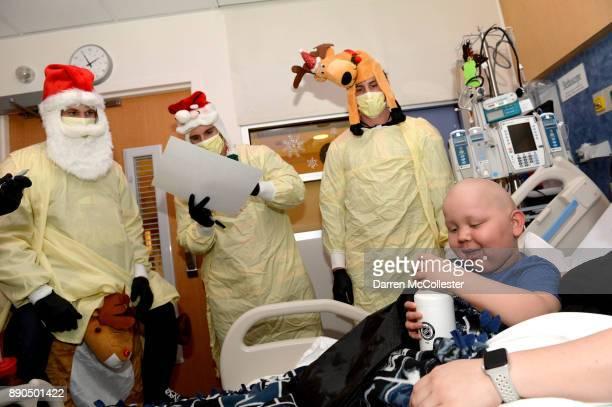 Boston Bruins Anders Bjork Noel Acciari and Tim Schaller visit with Lucas at Boston Children's Hospital December 11 2017 in Boston Massachusetts