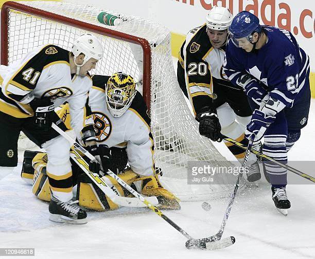 Boston Bruins Andrew Alberts and Wayne Primeau battle for the puck with Toronto's Alexei Ponikarovsky as Boston goaltender Tim Thomas hugs the goal...