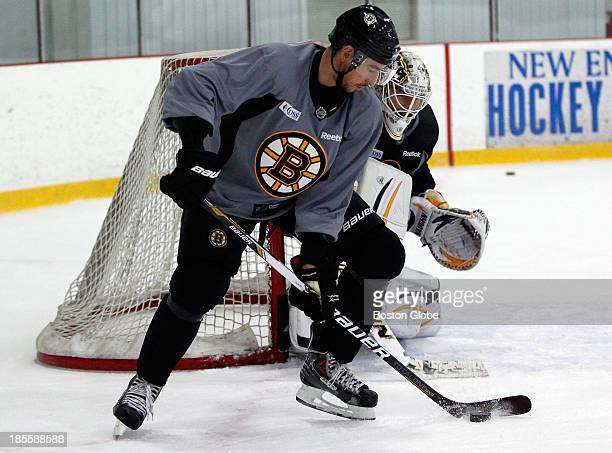 Boston Bruins Brad Marchand left shoots against Bruins Goalie Chad Johnson during practice in Wilmington Mass Oct 21 2013