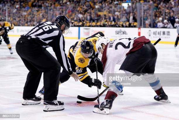 Boston Bruins center Austin Czarnik and Colorado Avalanche right wing Colin Wilson take a face off from linesman Michel Cormier during a game between...