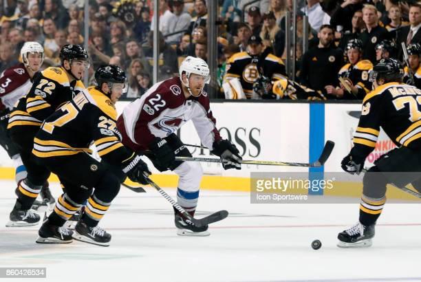 Boston Bruins center Austin Czarnik picks up the puck as Colorado Avalanche right wing Colin Wilson eyes Boston Bruins right defenseman Charlie...