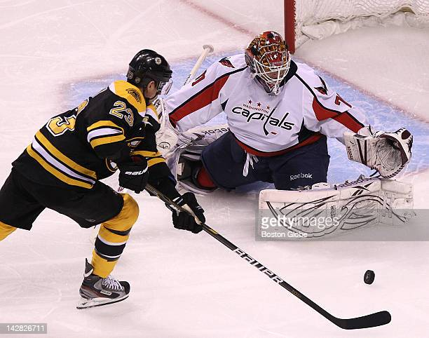 Boston Bruins center Chris Kelly pounces on a rebound but is unable to score on Washington Capitals goalie Braden Holtby during the first period...