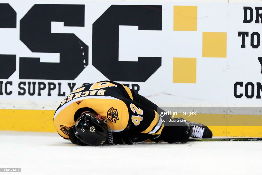 Boston Bruins center David Backes (42) down on the ice injured during a game between the Boston Bruins and the Anaheim Ducks on January 30, 2018, at TD Garden in Boston, Massachusetts. The Ducks defeated the Bruins 3-1.